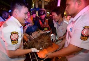 救護員在四面佛壇前抬走傷者。